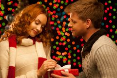 Young happy smiling casual couple making a present. Young happy smiling couple making a present over christmas tree and lights on background. shallow depth of stock photo