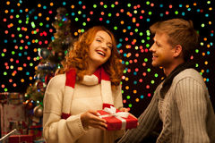 Young happy smiling casual couple making a present. Over christmas tree and lights on background. shallow depth of field. warm light royalty free stock photo