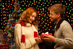 Young happy smiling casual couple making a present. Over christmas tree and lights on background. shallow depth of field. warm light Royalty Free Stock Photography