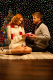 Young happy smiling casual couple making a present. Over christmas tree and lights on background. shallow depth of field. warm light Stock Images