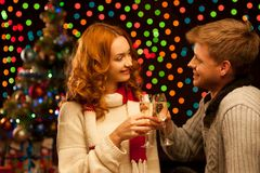 Young happy smiling casual couple with wineglasses. Young happy smiling couple with wineglasses over christmas tree and lights on background. shallow depth of stock image