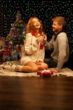 Young happy smiling casual couple with wineglasses. Over christmas tree and lights on background. shallow depth of field. warm light Stock Photo