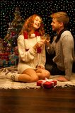 Young happy smiling casual couple with wineglasses. Over christmas tree and lights on background. shallow depth of field. warm light royalty free stock photography