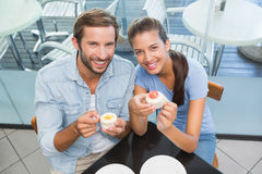 Young happy smiling couple eating cake while looking at the camera Stock Images