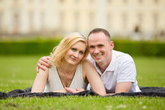 Young, happy and smiling couple lies on a grass Royalty Free Stock Images