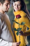 Young happy smiling couple with rose on romantic date. Young happy attractive smiling couple with rose on romantic date Royalty Free Stock Image