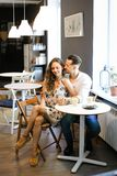 Young happy smiling couple sitting at cafe and resting. royalty free stock images