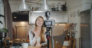 Young happy smiling European blonde woman travel blogger talks recording new vlog for social media at home slow motion. Beautiful female vlogger filming a new stock video footage