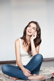 Young happy smiling girl with cell phone. Natural light portrait of young casual happy smiling caucasian brunette girl with cell phone Stock Photography