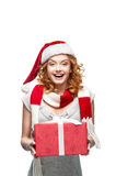 Young happy smiling girl holding christmas gift. Young red-haired european happy smiling girl in santa hat and red and white scarf holding christmas gift stock image