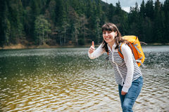 Young happy smiling girl with orange backpack standing on the bank of the mountain lake surrounded by forest showing like with han. D. Travel concept royalty free stock image