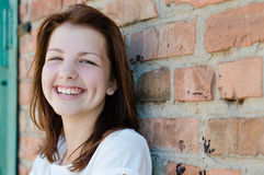 Young happy smiling girl standing at brick wall background Royalty Free Stock Photo