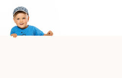Young happy smiling little boy look outs from the blank billboar. D Stock Images