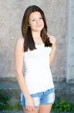 Young happy smiling & looking at camera girl standing at gray wall background copyspace Royalty Free Stock Photography