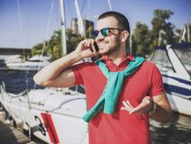 Young Happy Smiling Man in Glasses in Yacht Club. Guy in Red Shirt. Businessman in Sunglasses. Handsome Guy. Relaxed Man. Yacht on Water. Sunny on Sea. Rich stock images