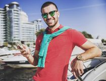 Young Happy Smiling Man in Glasses in Yacht Club. Guy in Red Shirt. Businessman in Sunglasses. Handsome Guy. Relaxed Man. Yacht on Water. Sunny on Sea. Rich stock photo