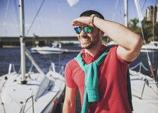 Young Happy Smiling Man in Glasses in Yacht Club. Guy in Red Shirt. Businessman in Sunglasses. Handsome Guy. Relaxed Man. Yacht on Water. Sunny on Sea. Rich stock image