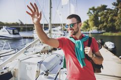 Young Happy Smiling Man in Glasses in Yacht Club. Guy in Red Shirt. Businessman in Sunglasses. Handsome Guy. Relaxed Man. Yacht on Water. Sunny on Sea. Rich stock photos
