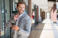 Young happy smiling man holding shopping bags and his mobile Royalty Free Stock Image