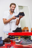 Young happy smiling man looking at the camera while holding a shoe Stock Photo