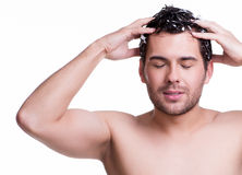 Young happy smiling man washing hair. Royalty Free Stock Photos