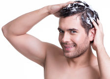 Young happy smiling man washing hair. Royalty Free Stock Images
