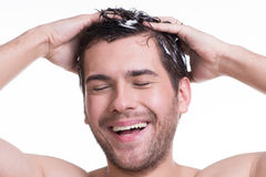 Young happy smiling man washing hair. Stock Photos