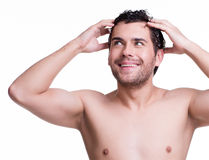 Young happy smiling man washing hair. Stock Photo