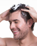 Young happy smiling man washing hair. Royalty Free Stock Image