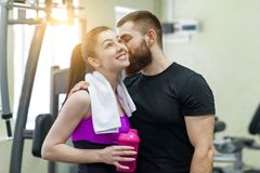 Young happy smiling man and woman talking embracing in gym. Sport, training, family and healthy lifestyle. Young happy smiling men and women talking embracing in royalty free stock photo