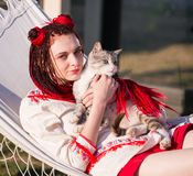 Young happy smiling red-haired girl dressed in hippie bohemian s. Tyle posing with a cat outdoors royalty free stock image