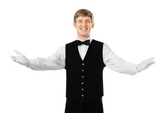 Young happy smiling waiter gesturing welcome. Portrait of young happy smiling waiter gesturing welcome isolated on white background Royalty Free Stock Image
