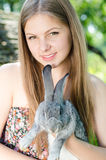 Young happy smiling woman embracing little rabbit outdoors Royalty Free Stock Images