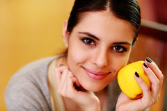 Young happy smiling woman holding yellow apple Stock Images