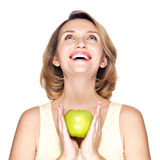 Young happy smiling woman holds green apple and looking up. Royalty Free Stock Photography