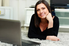 Young happy smiling woman lying on the floor with laptop Stock Images