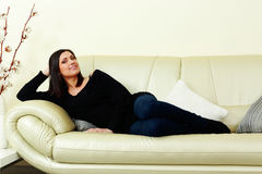 Young happy smiling woman lying on the sofa Royalty Free Stock Photos