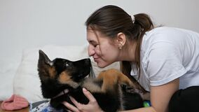 Young happy smiling woman playing and hugging a German shepherd puppy. Close-up indoors. The concept of care, education