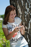 Young happy smiling woman reading message on mobile outdoors Stock Images