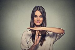 Young, happy, smiling woman showing time out gesture. Closeup portrait, young, happy, smiling woman showing time out gesture with hands isolated on gray wall Stock Photo