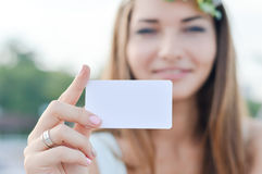 Young happy smiling woman shows blank business card Royalty Free Stock Photography