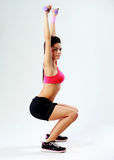 Young happy sport woman doing squats with dumbbells Stock Photo