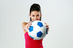 Young happy sport woman giving you a soccer ball Stock Photography