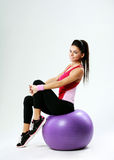 Young happy sport woman sitting on fitball Royalty Free Stock Images