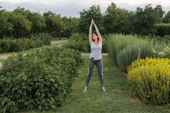 Young happy sporty woman stretching after jogging exercise in the city park stock photography