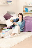 Young happy student have sandwich in living-room Royalty Free Stock Photography