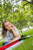 Young happy student lying on the grass on the phone Royalty Free Stock Photos