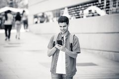 Happy young student male texting on his smart phone in modern city. Young happy student man in jeans denim clothes wearing sunglasses texting on his smart mobile Stock Photos