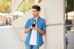 Happy young student male texting on his smart phone in modern city. Young happy student man in jeans denim clothes wearing sunglasses texting on his smart mobile Royalty Free Stock Images