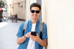 Happy young student male texting on his smart phone in modern city. Young happy student man in jeans denim clothes wearing sunglasses texting on his smart mobile Stock Photography